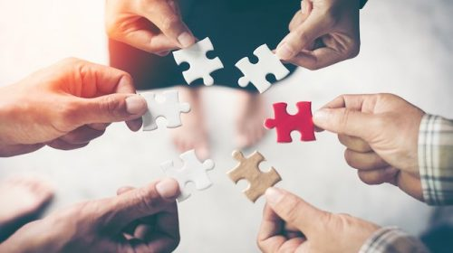 Hands holding piece of blank jigsaw puzzle for teamwork workplace success and strategy concept.