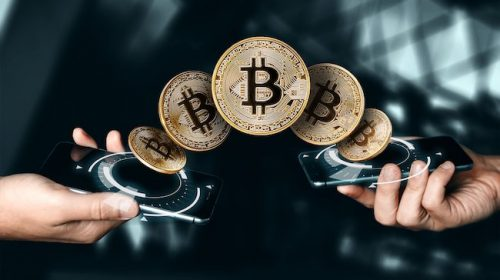 Gold coin Bitcoin payment from phone to phone, hands and TVs close-up. The concept of crypto currency. Blockchain technology.