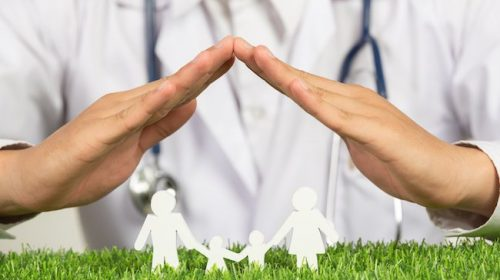 close up picture of doctor's hands posting symbol of home above family member model